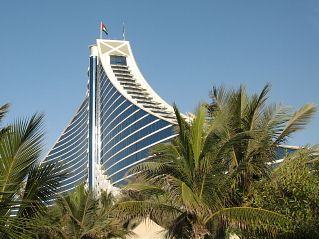 Jumeirah Beach Hotel in Dubai with palm trees in the foreground